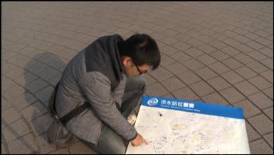 小銘哥蹲在淡水捷運站前的廣場,指著淡水街道地圖,說著他曾走過的路線。